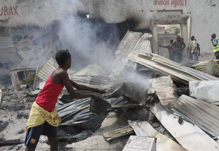 Un hombre rocía agua para extinguir las llamas tras un ataque suicida, en el Aeropuerto de Mogadiscio, Somalia. (EFE)