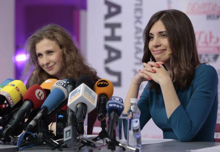 Las integrantes de la banda rusa punk Pussy Riot Nadezhda Tolokonnikova, a la derecha, y Maria Alekhina sonríen durante una conferencia de prensa en Moscú este viernes 27 de diciembre. (Agencias)