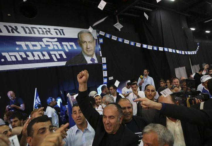 Simpatizantes del partido Likud del primer ministro israelí Benjamin Netanyahu (c) festejan el resultado de las elecciones de Israel, en Tel Aviv. (AP)