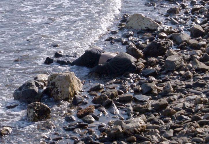 Imagen del cuerpo sin vida de una persona en la playa de Thermi, en la costa griega. (EFE)