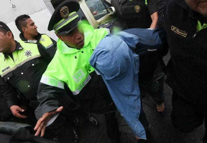 Momento en que uno de los delincuentes es sacado por la policía del poblado donde recibieron una golpiza por los habitantes. (twitter.com/diario24horas)