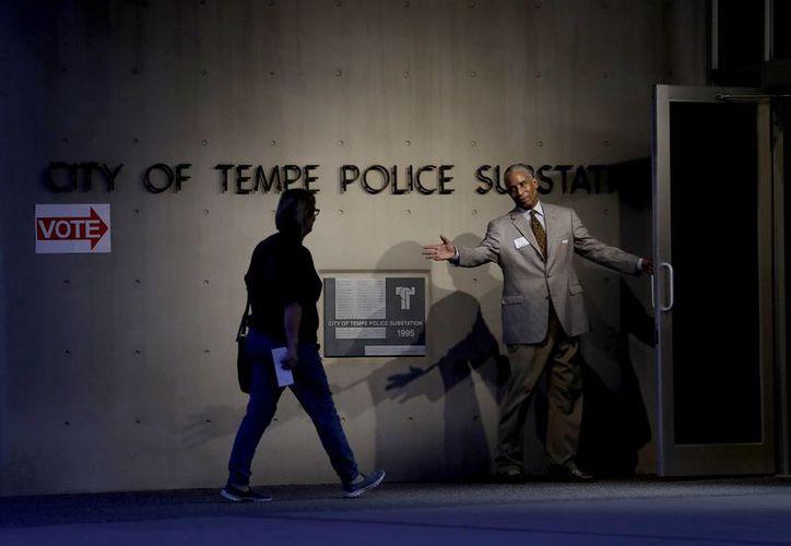 Un votante es recibido en la puerta de su centro de votación temprano, en Tempe, Arizona, uno de los estados que no presenta tendencia hacia alguno de los candidatos. (AP/Matt York)