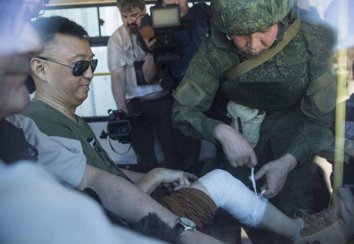 Un reportero chino es vendado por un oficial ruso después que una andanada de artillería hizo impacto en Kinsibba, Siria. (Agencias)