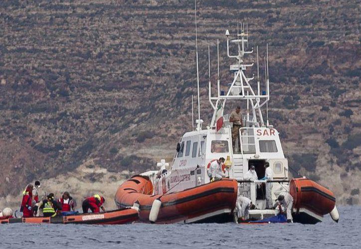 En la foto un barco italiano que rescató cuerpos de inmigrantes africanos, después del incendio y hundimiento de un navío frente a la isla de Lampedusa en octubre pasado. (Archivo Agencias)