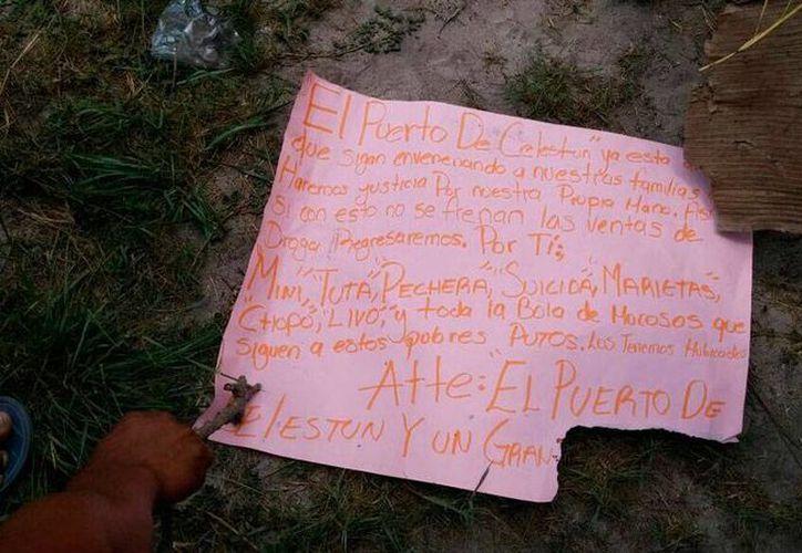 Imagen de uno de los dos mensajes de 'advertencia' que desconocidos dejaron en un campo deportivo, tras una balacera, en Celestún, que dejó como saldo dos heridos de gravedad. (SIPSE)