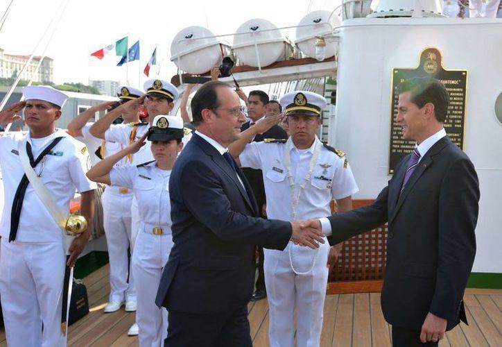"""El presidente Enrique Peña Nieto (d) dio la bienvenida al mandatario francés, Francois Hollande, a bordo del buque velero """"Cuauhtémoc"""", atracado en Marsella, Francia, el miércoles 15 de julio de 2015. (Notimex)"""