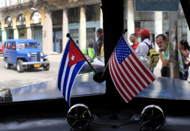 Fotografía de archivo de dos pequeñas banderas de Cuba y EU sobre el tablero de instrumentos de un automóvil en La Habana, Cuba. (Agencias)
