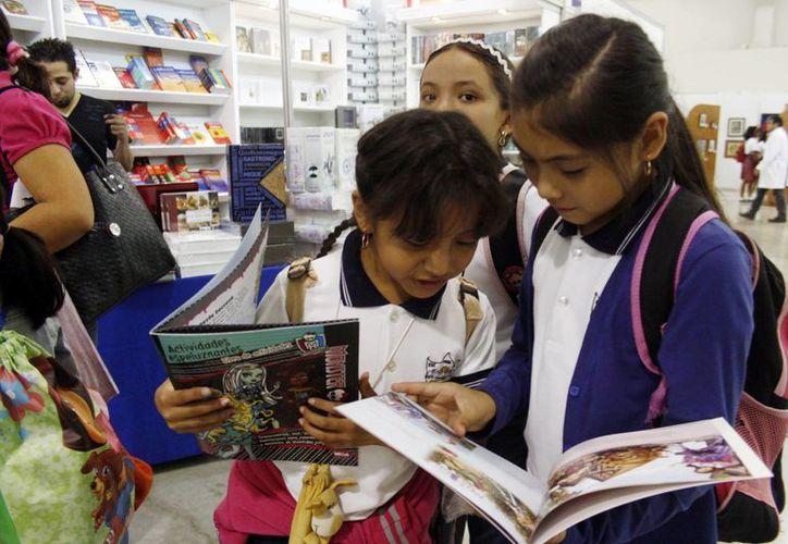 Autoridades yucatecas buscan que los menores lean más. En la imagen un grupo de niñas hojeando un libro de cuentos. (Milenio Novedades)