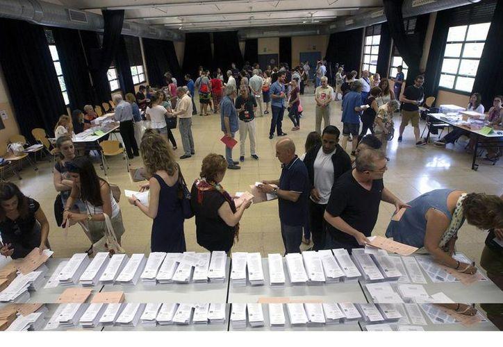 Varios ciudadanos eligen las papeletas en un colegio electoral de Barcelona, en la jornada de elecciones generales que se vivió hoy en España. (EFE)