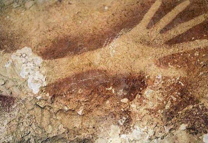 Fotografía facilitada por la revista Nature de las pinturas rupestres de 39 mil años de antigüedad descubiertas en la isla de Célebes, Indonesia. En la imagen una huella de mano. (EFE)