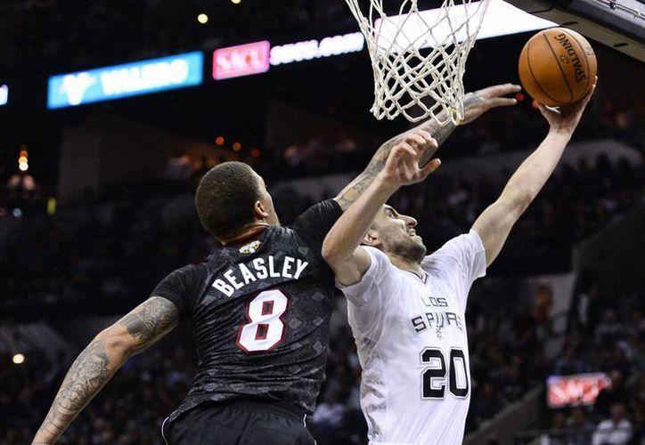 Michael Beasley, del Heat, bloque un tiro de Manu Ginobili, de Spurs. (EFE)
