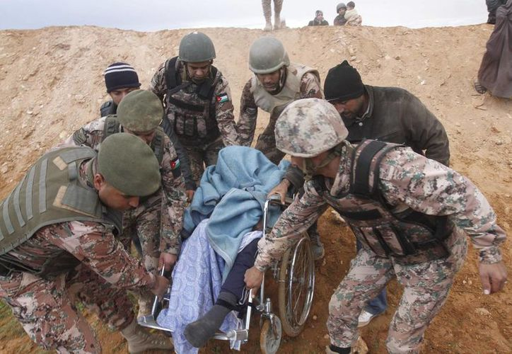 Soldados jordanos ayudan a un refugiado sirio enfermo en el este de la frontera entre Siria y Jordania. (EFE)