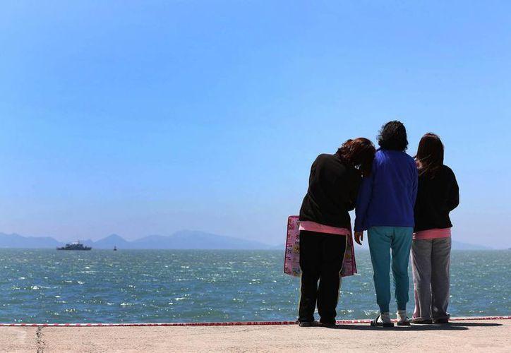 Los familiares de un pasajero a bordo del hundido barco Sewol miran hacia el mar en un puerto de Jindo, Corea del Sur. (Agencias)