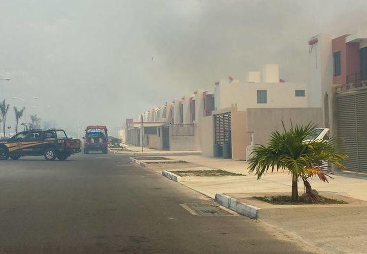Al fraccionamiento Los Héroes llegaron policías y bomberos para combatir el fuego. (Celia Franco/SIPSE)