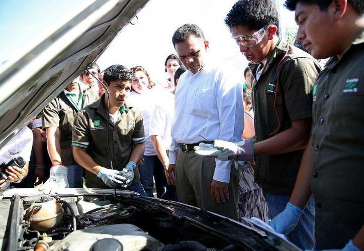 Los alumnos mostrar sus conocimientos sobre mecánica automotriz, uno de los varios servicios que ofrecerán gratuitamente a habitantes de colonias de Mérida. (Cortesía)