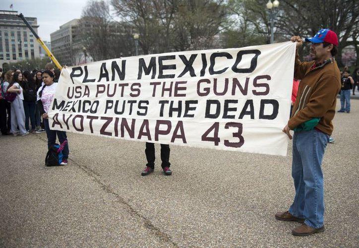 Decenas de personas participan en una concentración convocada frente a la Casa Blanca para mostrar su apoyo a los familiares de los 43 estudiantes de Ayotzinapa desaparecidos. (EFE)