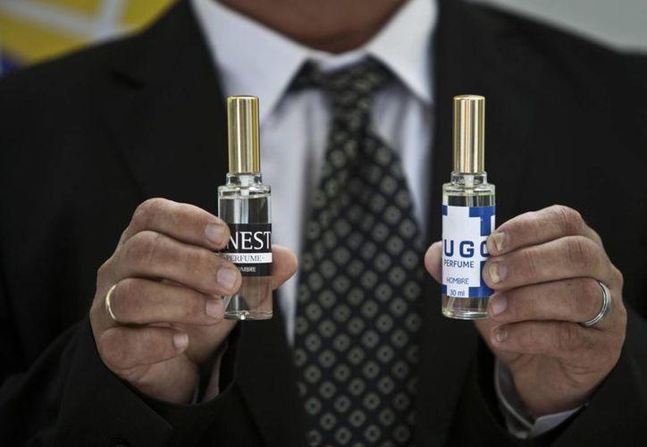 """Un hombre muestra dos botellas de perfume, uno llamado """"Ernesto"""" en honor al líder guerrillero Ernesto """"Che"""" Guevara, y otro """"Hugo"""" por el fallecido presidente venezolano Hugo Chávez, en La Habana, Cuba. (Agencias)"""
