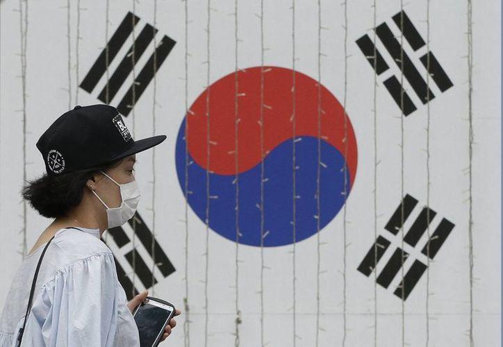 Una mujer usa una mascarilla como precaución contra el virus respiratorio MERS mientras pasa frente a una bandera de Corea del Sur, en Seúl. (Agencias)