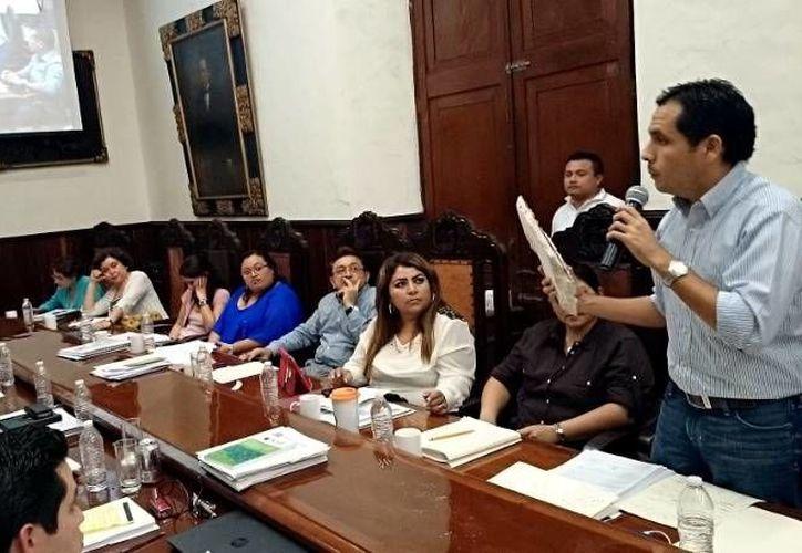 El regidor Rubén Segura Pérez exhibe ante el Alcalde y los regidores el pedazo de techo del mercado Lucas de Gálvez. (Cortesía)