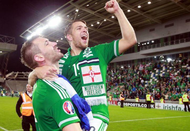 Gareth McAuley and Jamie Ward celebran la histórica e inédita calificación de Irlanda del Norte a la Eurocopa de 2016, gracias a que vencieron a Grecia en en estadio Windsor Park, en Belfast.  (AP)