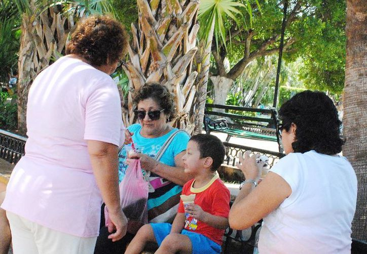 Los cambios bruscos de clima favorecen las IRA. Imagen de una familia que disfrutan de un helado en el centro de Mérida. (Milenio Novedades)