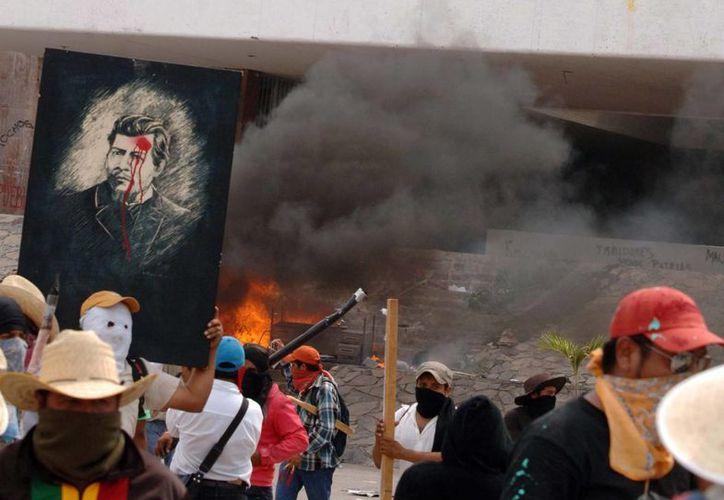 Los maestros arremetieron contra las instalaciones del PRI. (Notimex)