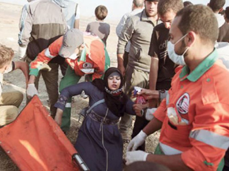 Palestinian medics help a woman who fainted from teargas fired by Israeli troops during a protest at the Gaza Strip's border with Israel. (AP)