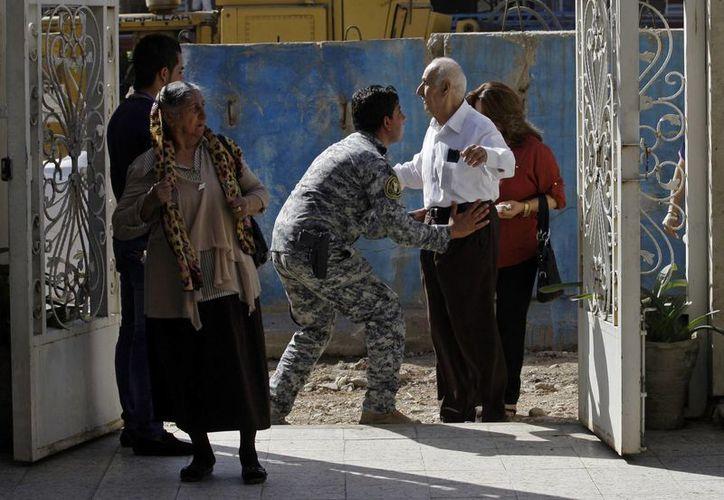 Un policía revisa a feligreses, en busca de armas, a las puertas de una iglesia en Irak. (Agencias)