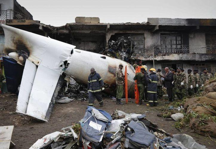 Oficiales de la policía inspeccionan la escena del accidente de un avión de carga en un suburbio de Nairobi, Kenia, hoy. (EFE)