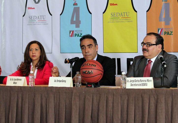 Enrique Garay (c), quien ya no forma parte de TV Azteca, aparece en esta foto durante la presentación del torneo estudiantil de nivel primaria hasta preparatoria, de basquetbol denominado '200 mil estudiantes por México'. (Notimex)