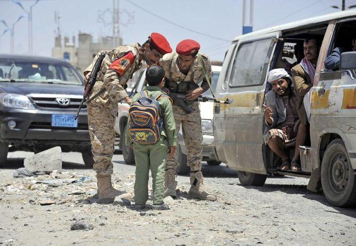 Soldados yemeníes, en el lugar donde un drone mató a diez miembros de Al Qaeda en Saná, Yemen, ayer. (EFE)