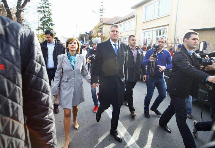 El candidato presidencial Klaus Iohannis (c) junto a su esposa Carmen Iohannis (iz) a su salida del centro de votación hoy en Bucarest. (EFE)