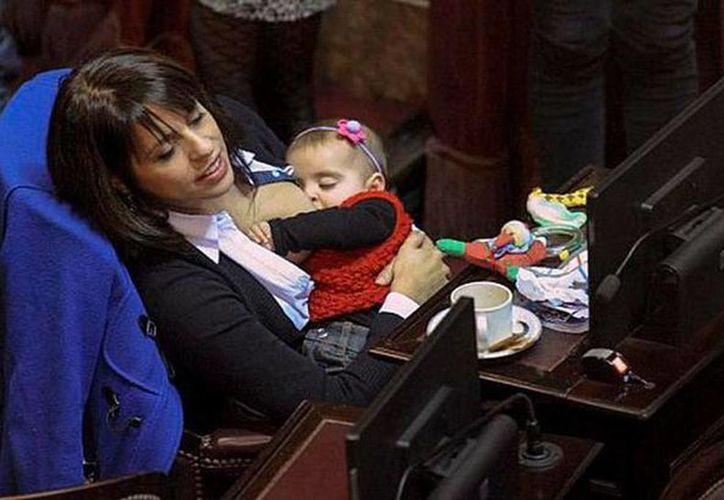 Imagen de la diputada Victoria Donda al momento de amamantar a su hija en una sesión del Congreso nacional de Argentina. (@sumariumcom)