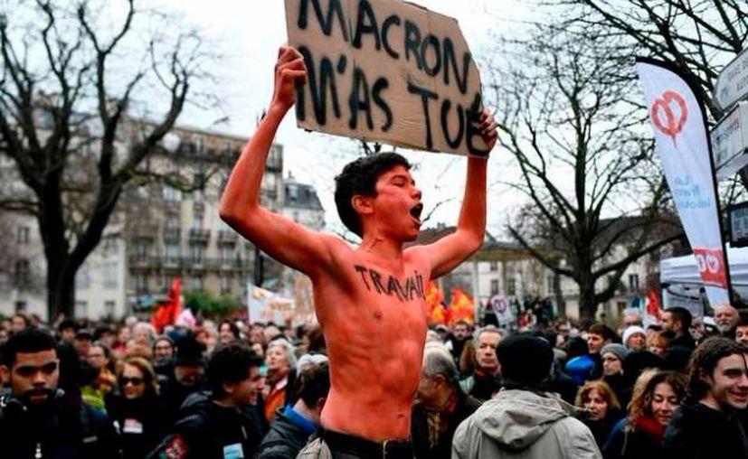 """Joven con una pancarta en la que se lee """"Macron me mató"""" y """"trabajo"""" escrito en el pecho, en protesta contra el gobierno francés. (Foto: AFP)"""