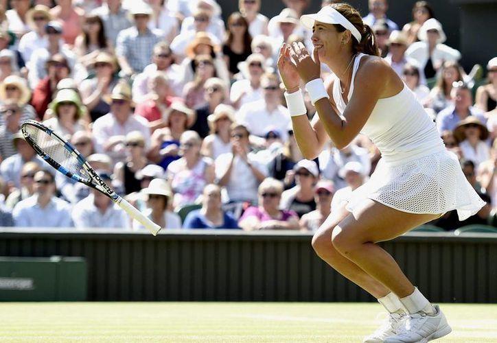 La tenista española Garbiñe Muguruza celebra su victoria ante la polaca Agnieszka Radwanska durante el partido de semifinales del torneo de tenis de Wimbledon. (EFE)