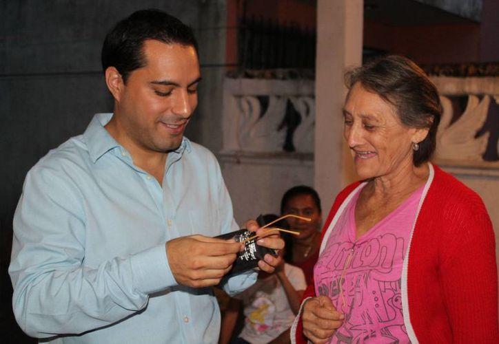 El diputado Mauricio Vila Dosal entrega un par de lentes a una vecina del fraccionamiento Juan Pablo II. (SIPSE)