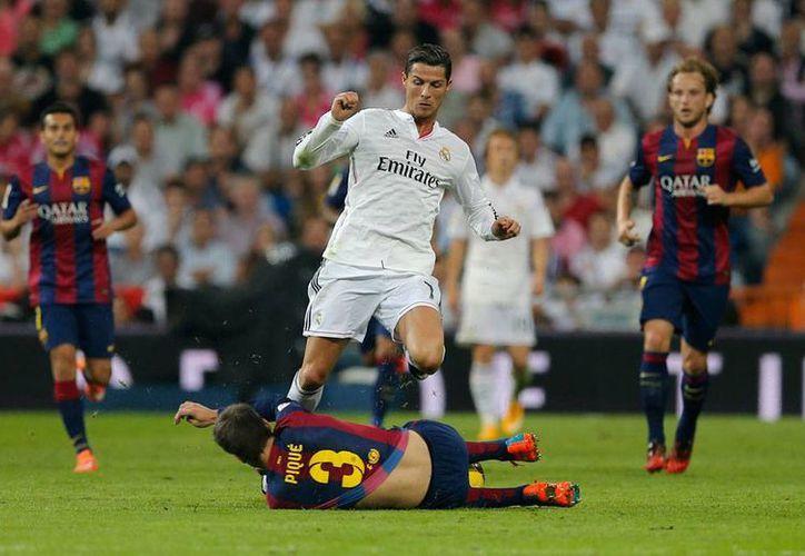 Héroe y villano: Cristiano Ronaldo diputa un balón con Gerard Piqué. Ambos también participaron en uno de los goles; el culé metió la mano en su área; el merengue metió el penalti para conseguir el gol del empate temporal. Real Madrid ganó 3-1 al Barcelona. (AP)