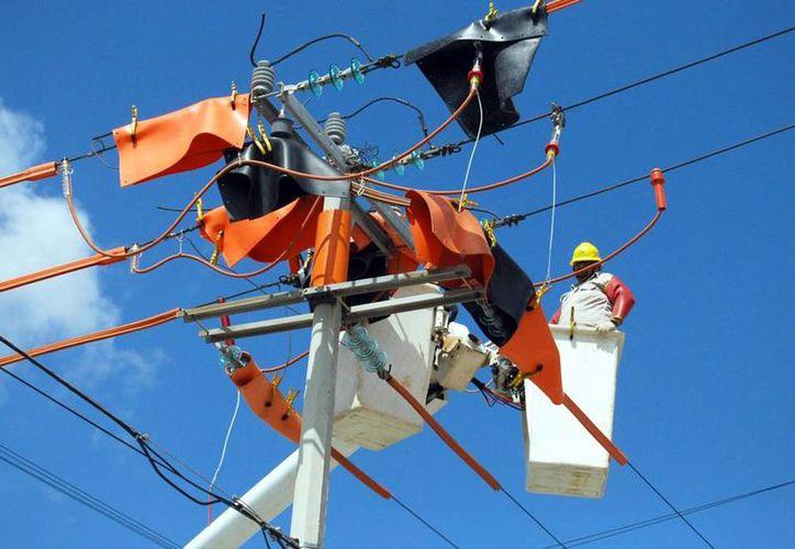 """Las tarifas de energía eléctrica están <i>por los aires</i>, pero la CFE dice que """"no le alcanza"""". Imagen de contexto: trabajadores de la paraestatal sustituyen cable de cobre en zonas de Cancún. (SIPSE.com)"""