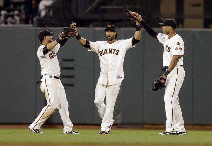 Jugadores de Gigantes: Gregor Blanco, Angel Pagan y Justin Maxwell, celebran tras vencer a Padres de San Diego. (Foto: AP)