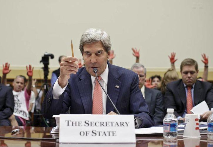 Los manifestantes sostenían sus manos pintadas de color rojo, de pie detrás de la secretaria de Estado estadounidense, John Kerry. (Agencias)