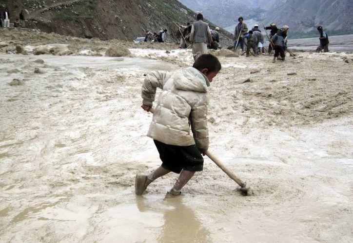 Varias personas intentan retirar el barro en una carretera tras una lluvia torrencial seguida de un desprendimiento de tierra en la provincia de Badakhshan, en Afganistán. (EFE)