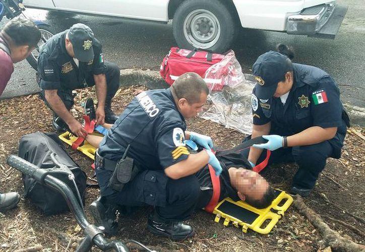 El conductor del volquete le cerró el paso al motociclista quien acabó con serias lesiones en el cuerpo. Imagen del momento en que paramédicos atendían al lesionado. (SIPSE)