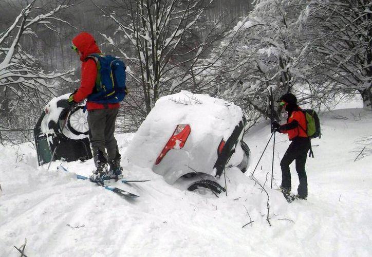 Los rescatistas están de pie junto a dos coches sumergidos en la nieve mientras trabajan frente al Hotel Rigopiano, luego de una avalancha en Farindola, Italia. (Corpo Nazionale Soccorso Alpino e Speleologico / CNSAS a través de AP)