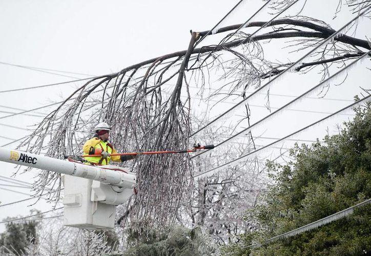 La tormenta de nieve dejó a miles de personas sin electricidad porque el peso del hielo que cayó sobre los tendidos echó abajo varios tramos de la red eléctrica. Un trabajador 'libera' unos cables en Frederick, Maryland. (Agencias)
