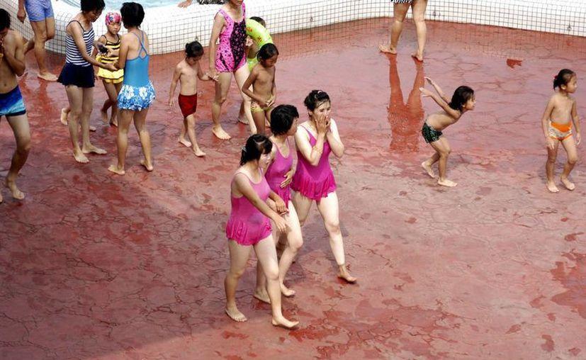 Las mujeres norcoreanas aún consideran impensable enseñar el ombligo, incluso en un parque al que acuden a refrescarse. (EFE)