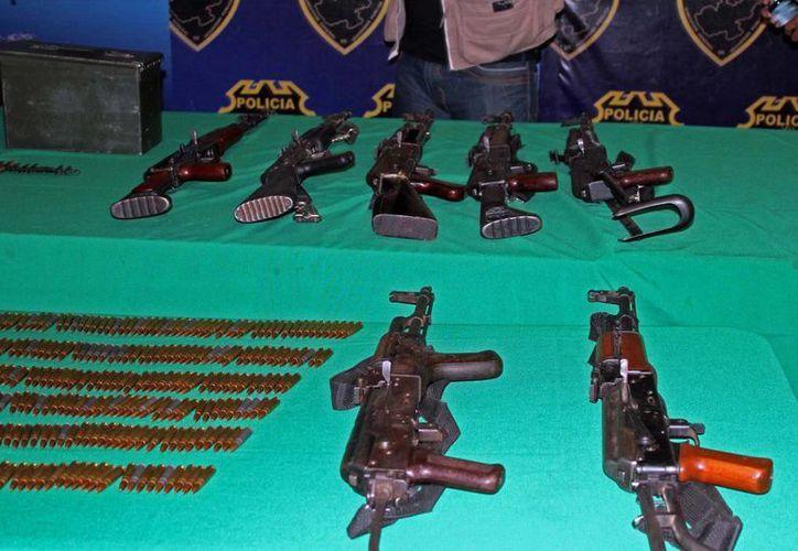 En el lugar se localizaron 17 armas largas, 47 cargadores, 700 cartuchos útiles, ocho cascos y droga. (Notimex)