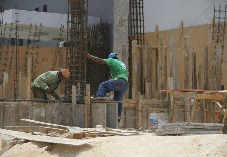 La posición geográfica y la mano de obra son las principales apuestas para ofertar a las nuevas industrias que llegan al Estado. Fotografía de trabajadores de la construcción en una obra. (Archivo/SIPSE)
