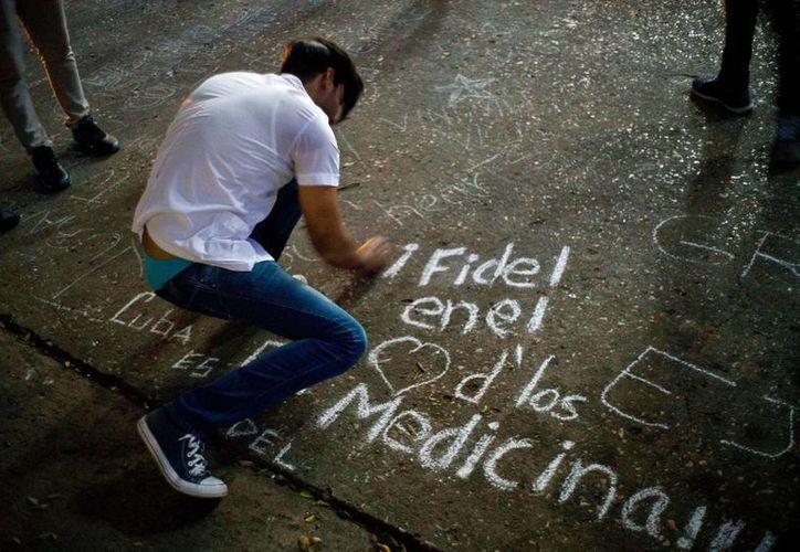 """Un estudiante escribe en una acera con tiza """"Fidel en el corazón de los estudiantes de medicina"""" durante una vigilia por el fallecido líder cubano Fidel Castro en la universidad donde Castro estudió derecho de joven en La Habana, Cuba, el sábado 26 de noviembre de 2016. (AP Foto/Ramon Espinosa)"""
