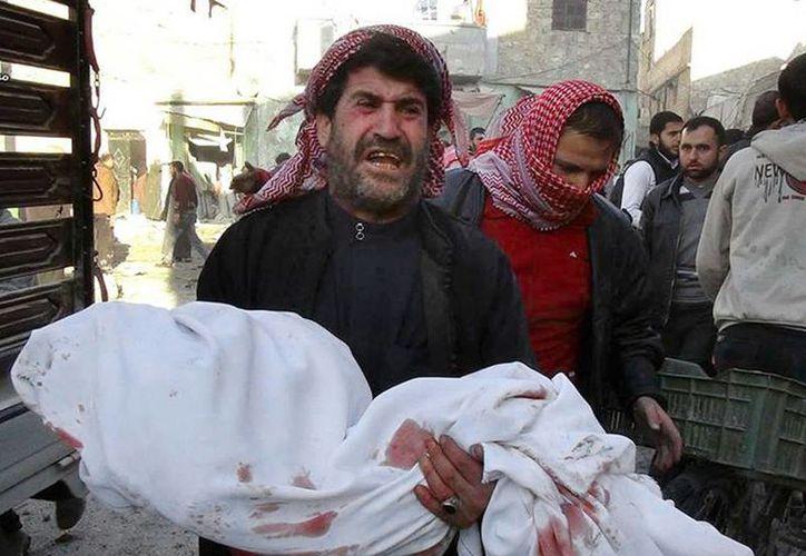 Una hombre sostiene el cadáver de un niño, víctima de los ataques aéreos del régimen en el norte de Alepo, la principal ciudad de Siria. En los bombardeos de este lunes, los activistas reportan más de una decena de muertos. (Agencias)