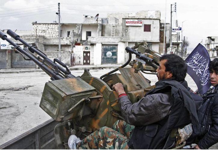 Combatientes del Ejército sirio manipulan una ametralladora antiaérea en Aleppo. (AP)